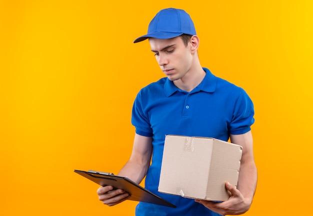 Il giovane corriere che indossa l'uniforme blu e il berretto blu guarda negli appunti e tiene una scatola
