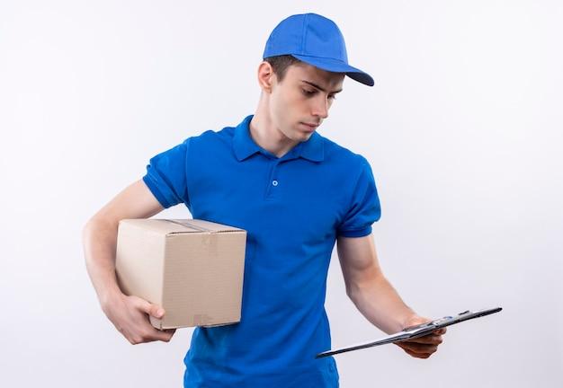 Il giovane corriere che porta l'uniforme blu e la protezione blu esamina il telefono e tiene una scatola