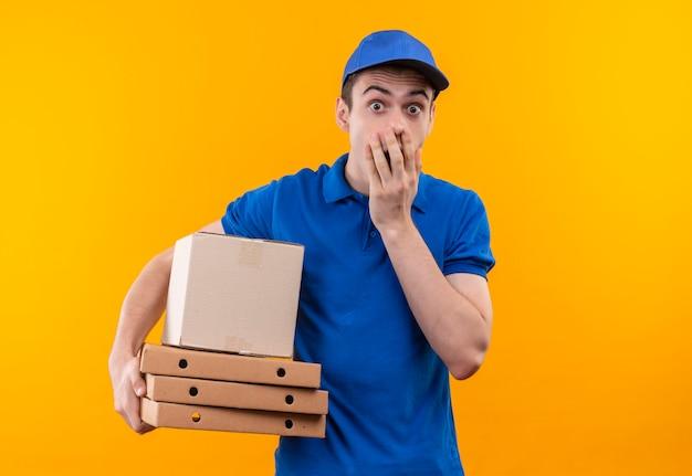 Il giovane corriere che indossa l'uniforme blu e il berretto blu spaventato chiude il suo mouse con la mano e tiene le scatole