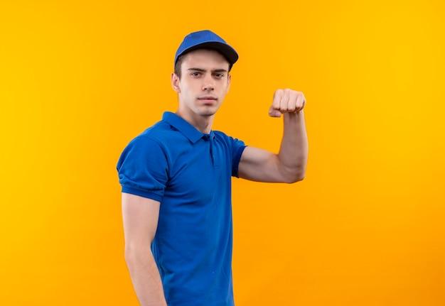 Il giovane corriere che indossa l'uniforme blu e il berretto blu mostra potenza con il pugno