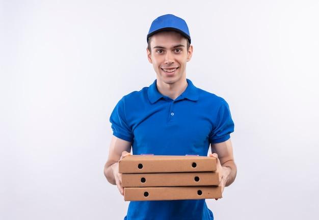 Il giovane corriere che indossa l'uniforme blu e il berretto blu sorride e tiene le scatole