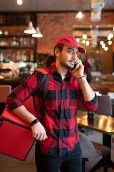 어깨에 큰 빨간 가방이 달린 젊은 택배가 고객 중 한 명에게 전화하여 주문 배송에 적합한 주소와 시간을 지정합니다.