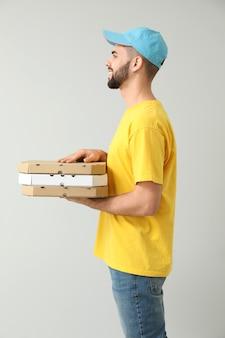 明るい表面にピザの箱を持つ若い宅配便