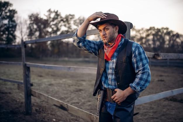 Молодой ковбой в кожаной куртке и шляпе позирует на фоне конного загона