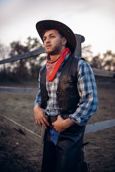 Young cowboy poses against horse corral