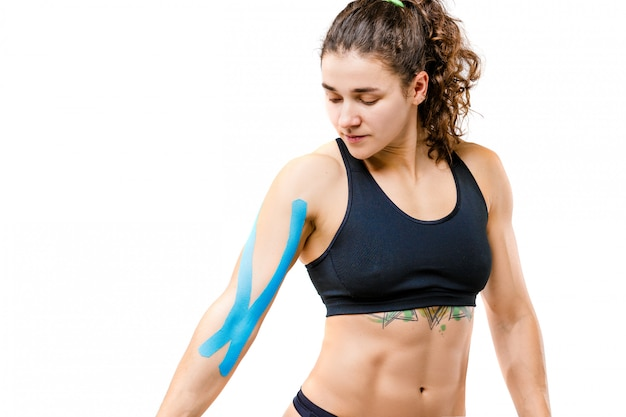 A young cowish girl with a good figure posing on a white isolated background with a kinesiology tape