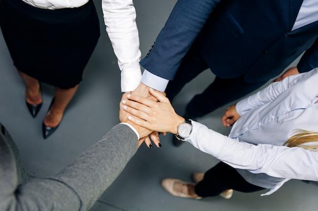 사무실에서 화합의 상징으로 손을 모으는 젊은 동료