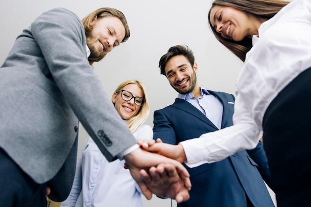 Молодые сотрудники складывают руки вместе как символ единства в офисе