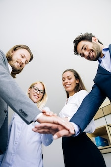 Young coworkers putting hands together as symbol of unity in the office