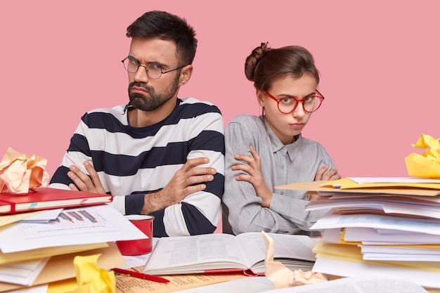 Молодые коллеги, сидя за столом с документами