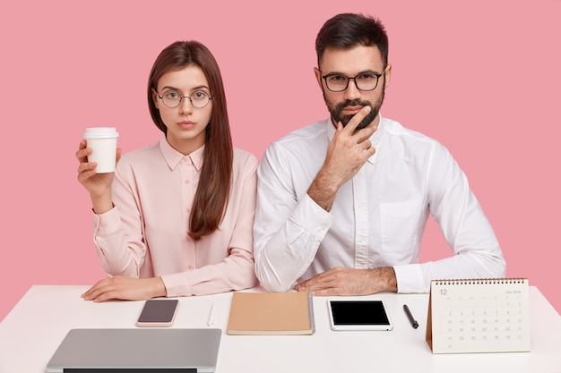 Young coworkers sitting at desk with gadgets and calendar