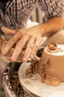 Молодой мастер с помощью ручного инструмента выровняет поверхность нового глиняного изделия на гончарном круге при изготовлении фаянса