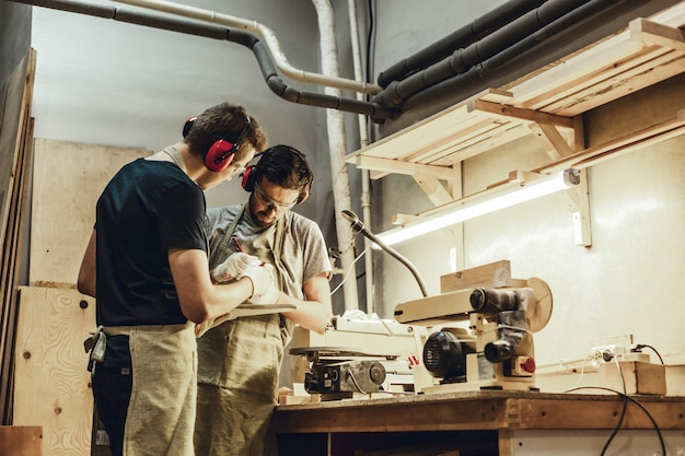 Young craftsmen drafting near workbench