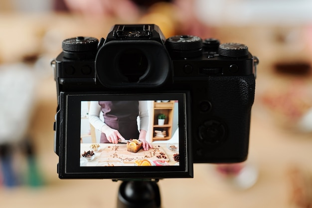 Young craftswoman in camera during video recording of home master class of making handmade soap