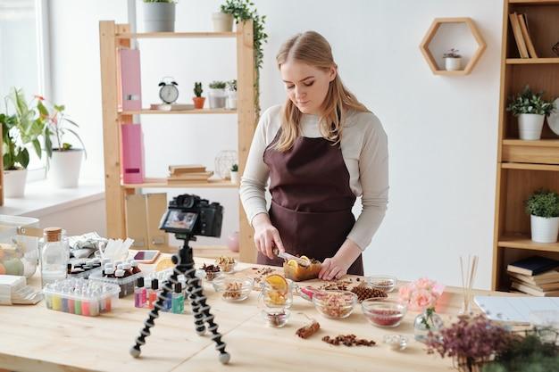 Молодая мастерица снимает домашний мастер-класс на камеру, стоя у стола и режет большой кусок мыла ручной работы