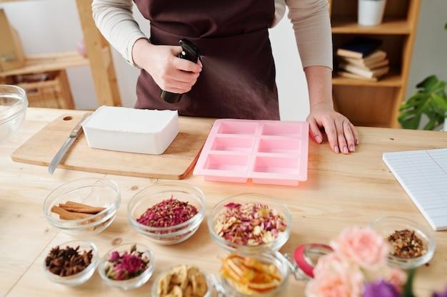 Молодая мастерица распыляет масло на розовые силиконовые формы, готовя их к заливке жидкой мыльной массы