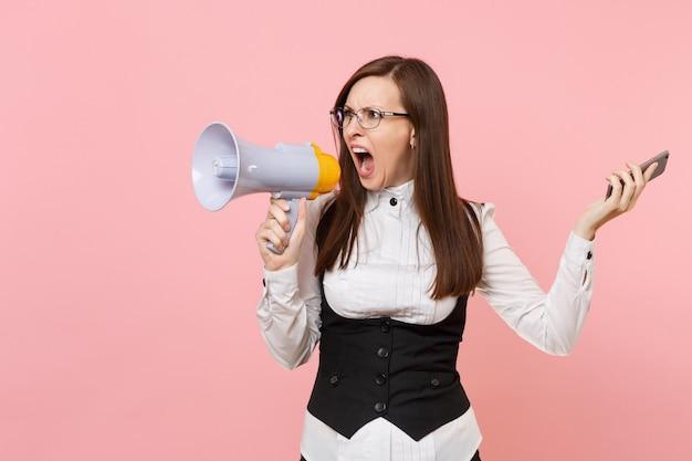 Молодая сумасшедшая злая бизнес-леди в черном костюме, кричащих очках, держащей мегафон и мобильный телефон, изолированные на розовом фоне. леди босс. достижение карьерного богатства. скопируйте место для рекламы.