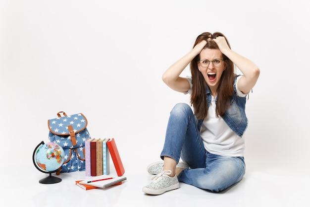Giovane studentessa arrabbiata pazza in vestiti di denim che urla aggrappandosi alla testa seduta vicino al globo, libri di scuola zaino isolati