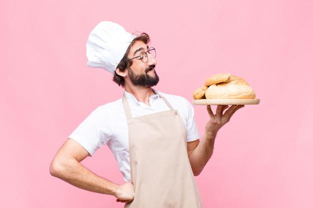 Молодой сумасшедший пекарь держит хлеб на розовой стене