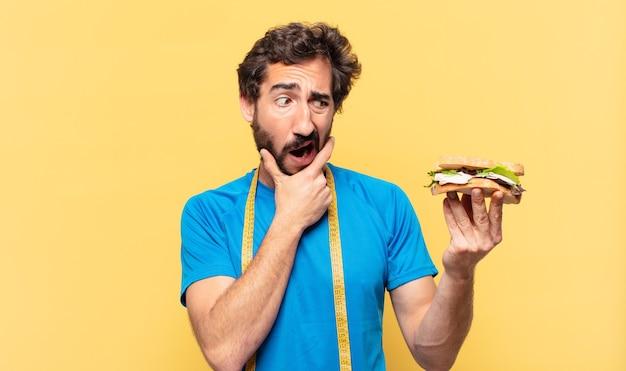 Молодой сумасшедший бородатый спортсмен, сомневающийся или неуверенное выражение и концепция диеты