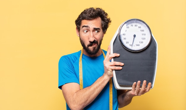 Young crazy bearded athlete doubting or uncertain expression and diet concept and holding a scale