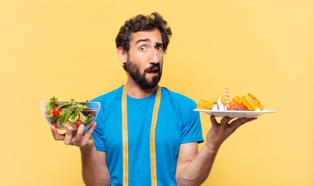 Young crazy bearded athlete doubting or uncertain expression and diet concept