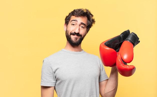 若い狂気のひげを生やしたアスリートの幸せな表情とボクシンググローブを保持しています