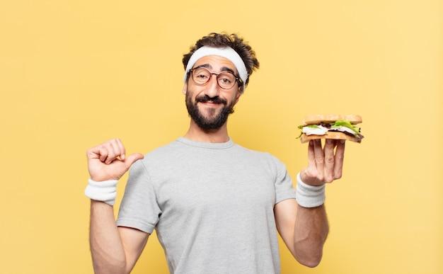 Молодой сумасшедший бородатый спортсмен счастливое выражение и держит бутерброд