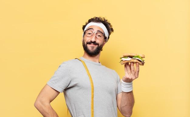 Молодой сумасшедший бородатый спортсмен счастливым выражением лица и держит бутерброд