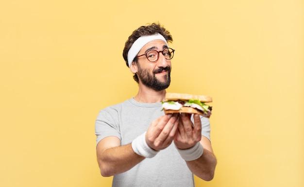 젊은 미친 수염된 운동 선수 행복한 표정과 샌드위치를 들고
