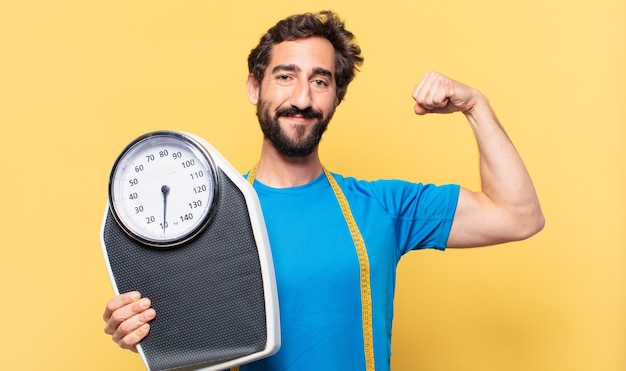Young crazy bearded athlete happy expression and diet concept and holding a scale