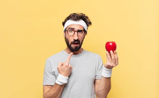 Молодой сумасшедший бородатый спортсмен с грустным выражением лица и держит яблоко и держит яблоко
