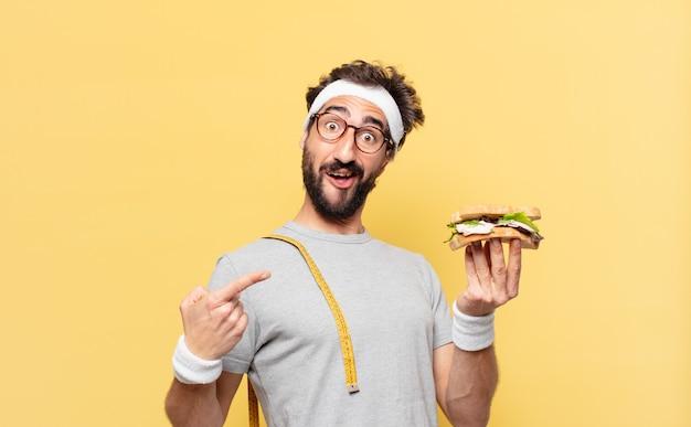 若い狂ったひげを生やしたアスリートは、表情を驚かせ、サンドイッチを持っています