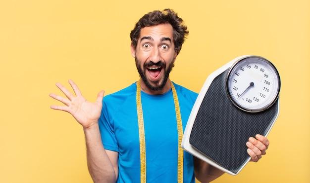 Young crazy bearded athlete surprised expression and diet concept and holding a scale