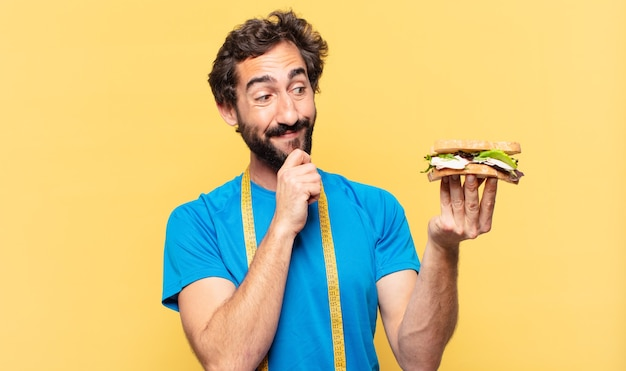 Молодой сумасшедший бородатый спортсмен мышления и концепция диеты