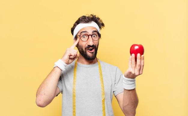 Молодой сумасшедший бородатый спортсмен думает выражение и держит яблоко