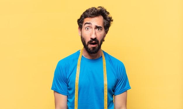 Молодой сумасшедший бородатый спортсмен с грустным выражением лица и концепцией диеты