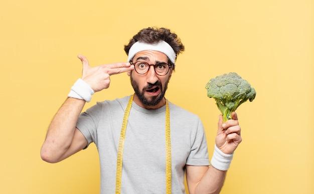 Молодой сумасшедший бородатый спортсмен с грустным выражением лица держит цветную капусту