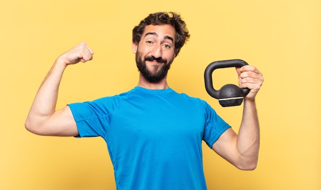 Young crazy bearded athlete young crazy bearded athlete happy expression and lifting a dumbbell