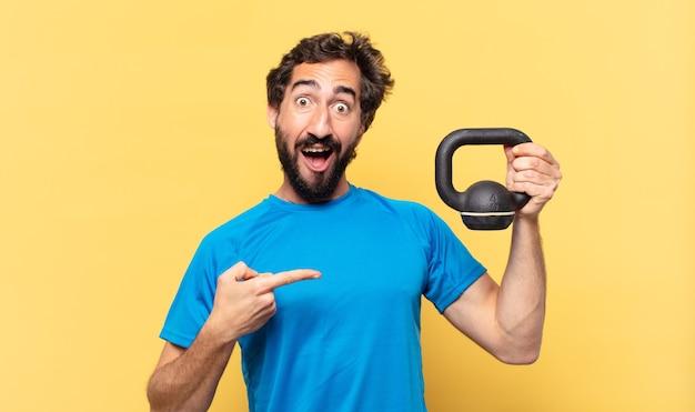 젊고 미친 수염 난 운동 선수 아령을 가리키거나 보여주고 들어 올리는 젊은 미친 수염 운동 선수