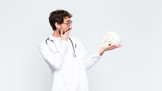 人間の頭蓋骨を保持している若いクレイジーひげを生やした医者