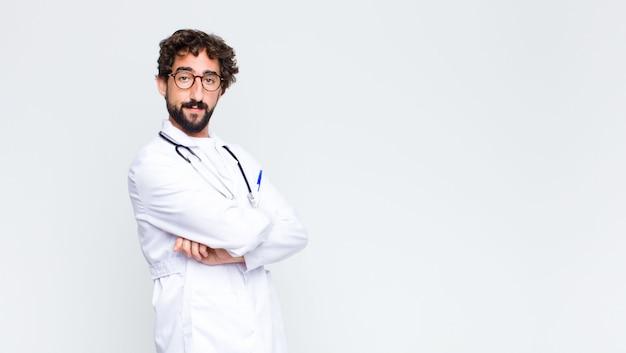 Молодой сумасшедший бородатый врач против стены копией пространства