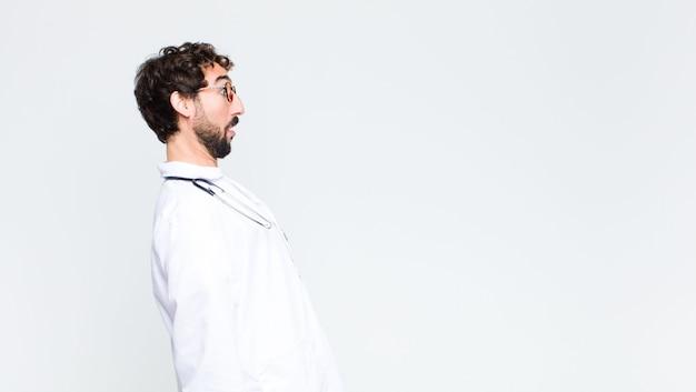コピースペースの壁に対して若いクレイジーひげを生やした医者男