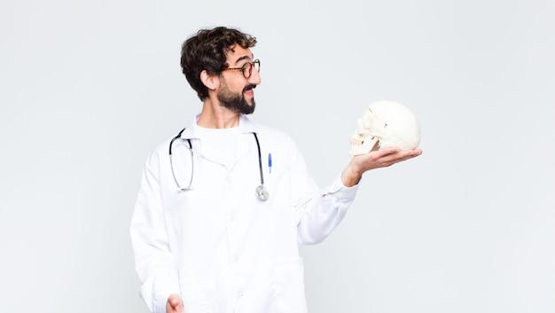 人間の頭蓋骨を保持している若いクレイジーひげを生やした医者男