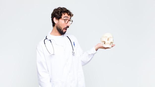 若いクレイジーひげを生やした医者人間の頭蓋骨を保持