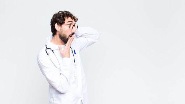 Молодой сумасшедший бородатый врач мужчина на копией пространства стены