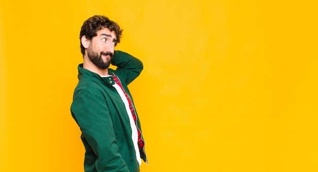 Young crazy bearded man against orange wall