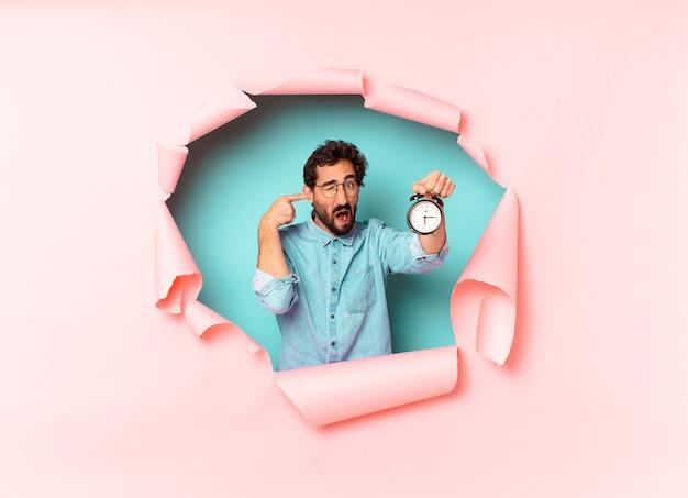 Young crazy bearded man. alarm clock concept