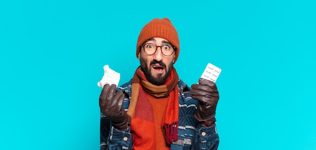 若い狂ったひげを生やした男と冬の服を着ています。病気の概念