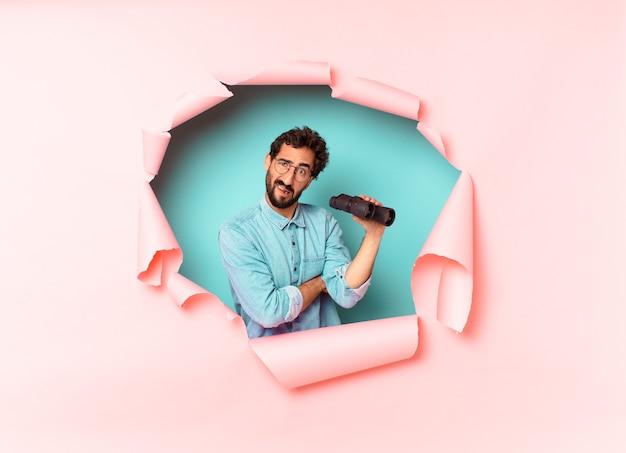 Young crazy bearded man. binoculars concept